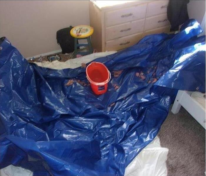 Bedroom with leaking ceiling into a bucket on a tarp