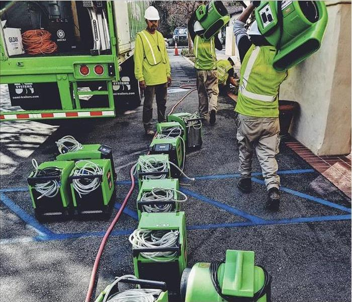 SERVPRO crews carrying equipment